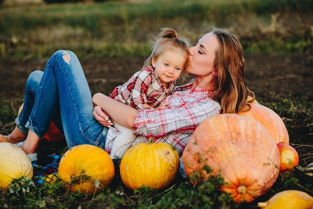 Mère et fille se trouvent entre les citrouilles sur le terrain