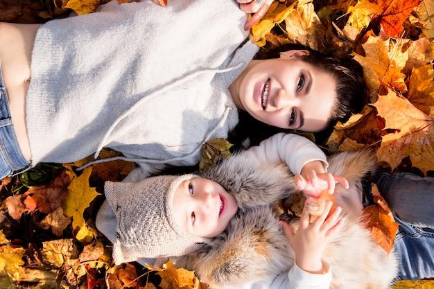 Mère et fille se trouvent sur les feuilles d'automne