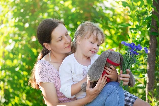 Mère et fille sont assises sur un banc dans le jardin