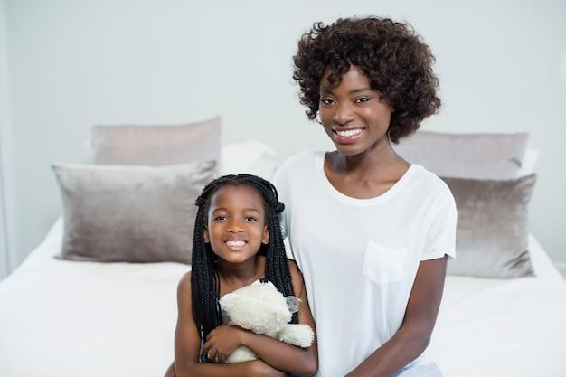 Mère et fille souriante dans la chambre à la maison