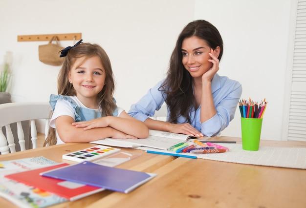Mère et fille souriante se préparant pour les leçons et dessine à la table avec des crayons et des peintures