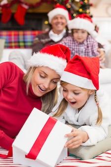 Mère et fille surpris d'ouvrir un cadeau de noël