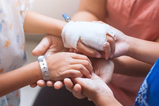 Mère et fille tenant la main avec une solution intraveineuse bandée avec amour et soin
