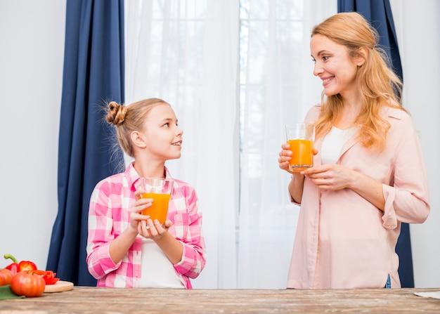 Mère et fille tenant un verre de jus dans la main se regardant
