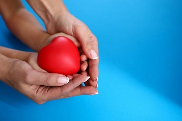Mère et fille tiennent coeur rouge contre bleu