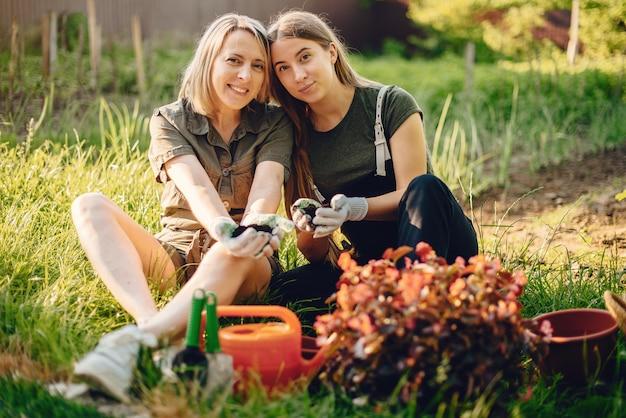 Mère avec une fille travaille dans un jardin près de la maison