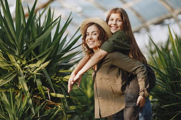 Mère avec fille. travailleurs avec des pots de fleurs. fille dans une chemise verte