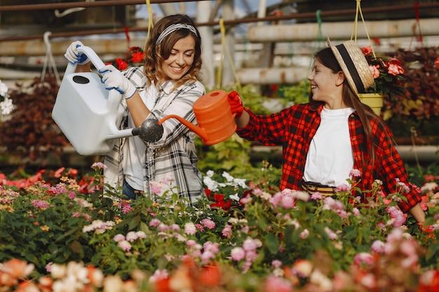 Mère avec fille. travailleurs avec des pots de fleurs. les gens versent des fleurs
