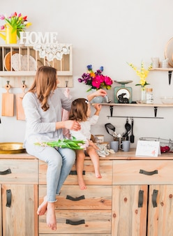 Mère et fille avec des tulipes assis sur une table