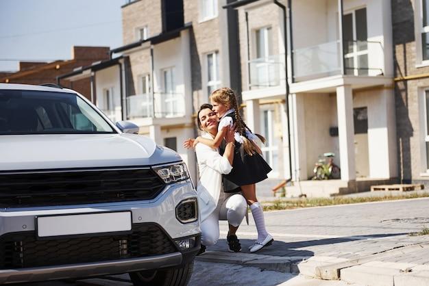 Mère avec fille en uniforme scolaire à l'extérieur près d'une voiture blanche.