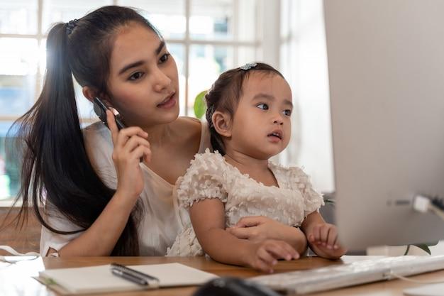 Mère et fille utilisant un ordinateur et internet pendant que la mère travaille à domicile