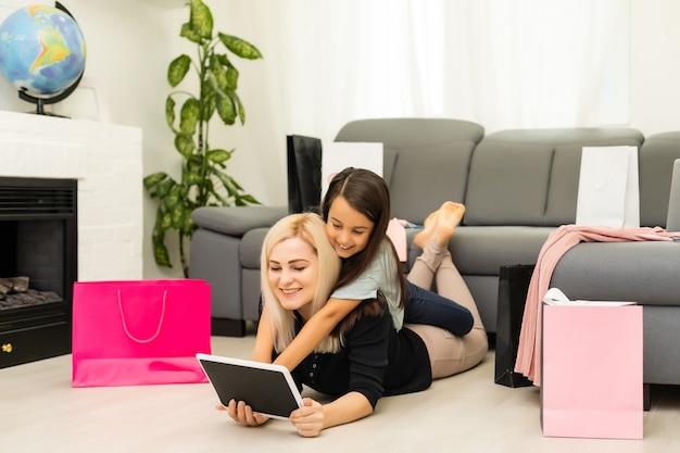 La mère et la fille utilisent une tablette pour acheter des choses en ligne le vendredi noir