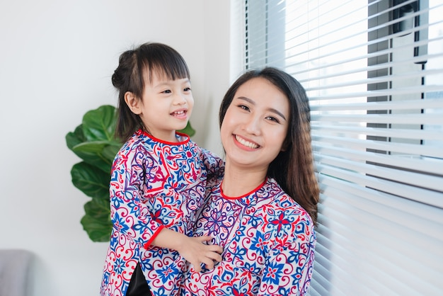 Mère et fille vietnamiennes en costume traditionnel ao dai, célèbrent le nouvel an à la maison. vacances du têt.