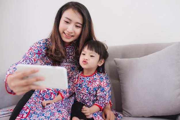 Mère et fille vietnamiennes en costume traditionnel ao dai, prenant une photo de selfie.
