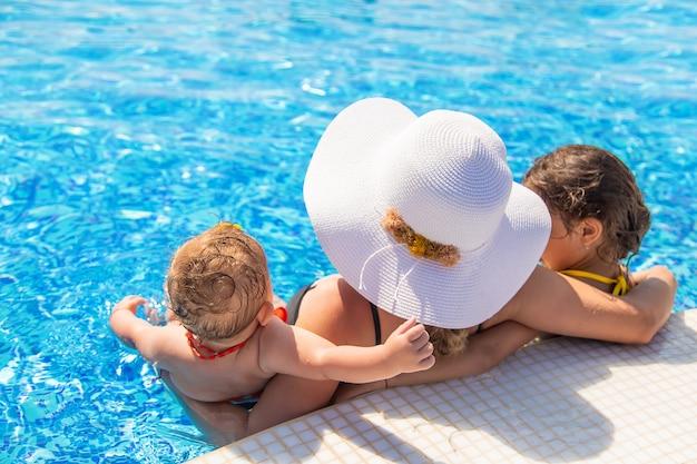 Mère avec filles dans la piscine. mise au point sélective. gens.