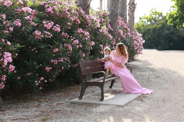 Mère et filles dans des robes similaires, assis dans le parc.