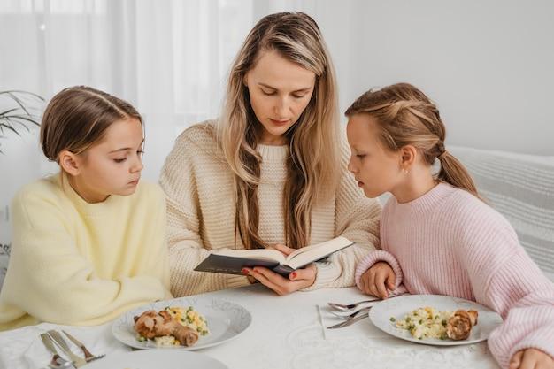 Mère et filles priant à table