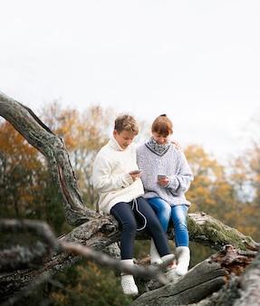 Mère et fils adolescent s'asseoir dos ensemble sur une branche d'arbre et utiliser des téléphones portables et des casques