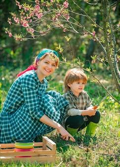 Mère et fils agriculteurs à la ferme avec fond de campagne eco farm happy family gardener carryi...