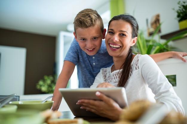 Mère et fils à l'aide de tablette numérique dans le salon