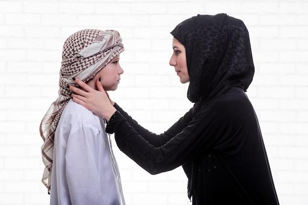Mère et fils arabes posant à l'intérieur.