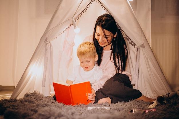 Mère avec fils assis dans une tente confortable avec des lumières à la maison à noël