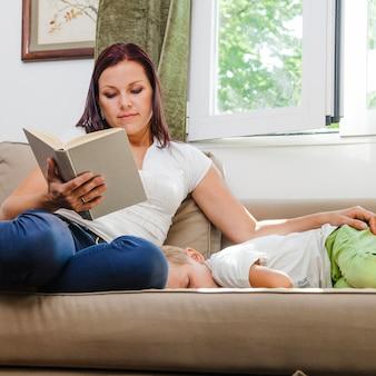 Mère avec fils assis sur le sofa reading