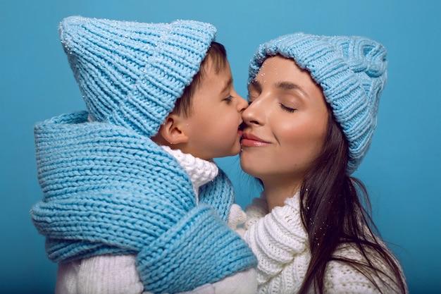 Mère et fils en chandails blancs et chapeaux bleus se tiennent sur un bleu dans le studio