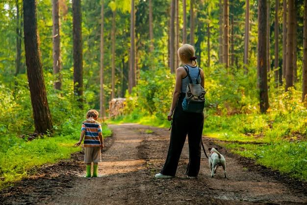 Mère avec un fils et un chien dans une forêt