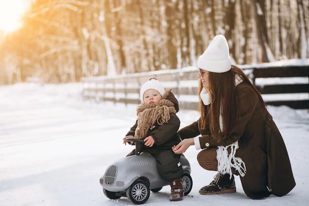 Mère avec fils dans la petite voiture à l'extérieur en hiver