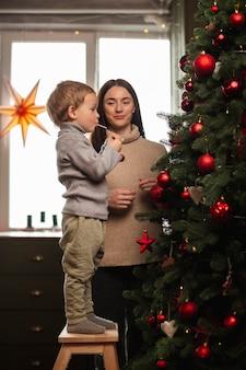 Mère et fils décorant le sapin de noël