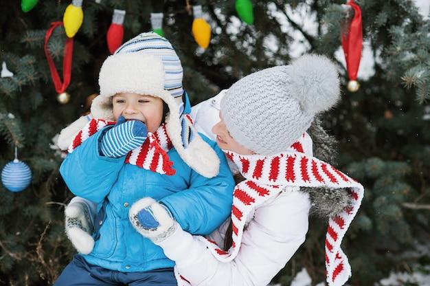 Mère et fils décorer le sapin de noël en plein air dans un parc d'hiver,