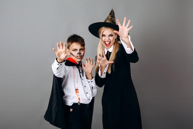 Mère et fils en déguisements montrant un geste effrayant à la caméra. halloween