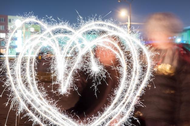 Mère et fils dessinant un coeur avec des baguettes scintillantes.