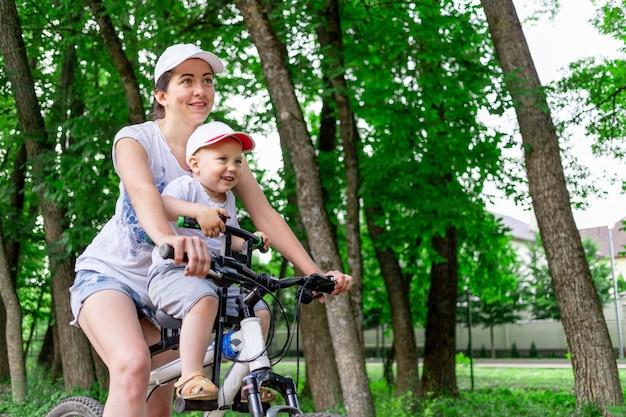 Mère et fils faire du vélo, la mère porte un enfant dans une chaise d'enfant sur un vélo dans le parc en été