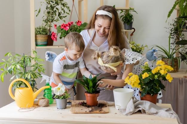 Mère avec fils et fille dans une plante à jeun ou transplanter des fleurs d'intérieur petite aide par les tâches ménagères