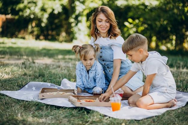 Mère avec fils et fille mangeant de la pizza dans le parc