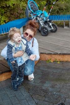 Mère et fils handicapé marchent à l'air frais sur une chaise, mère et bébé sourire