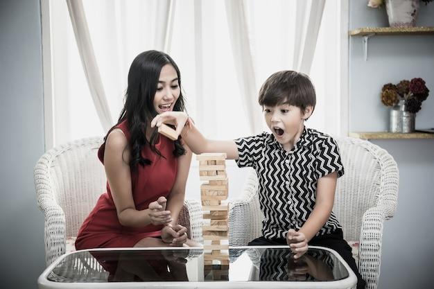 Mère et fils jouant au jeu de jenga. bonne famille de temps.