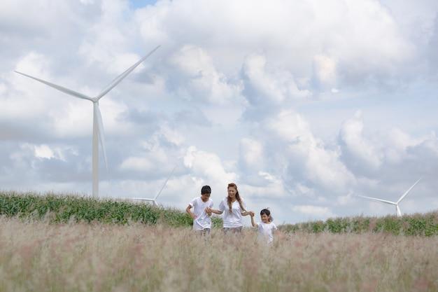 Mère et fils jouant dans déposé avec une énorme éolienne en arrière-plan
