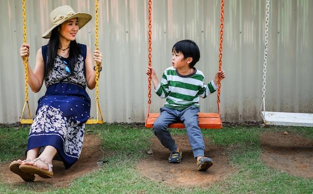 Mère et fils jouent swing dans la cour de récréation en vacances
