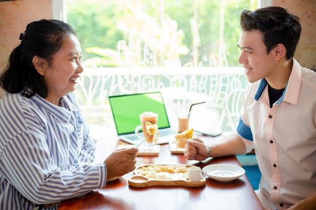 Mère et fils mangeant des pâtisseries croustillantes