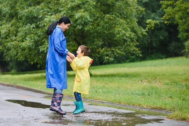 Mère avec fils marchant dans le parc sous la pluie portant des bottes en caoutchouc