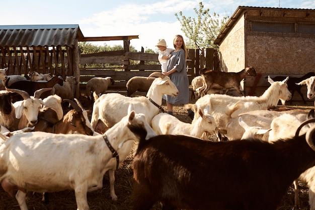 Mère et fils marchant parmi les animaux de la ferme