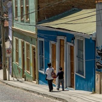 Mère et fils marchant sur la rue le long des maisons, valparaiso, chili