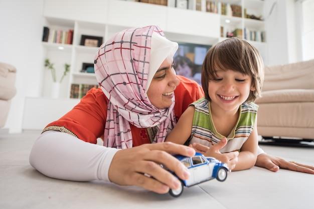 Mère et fils mignon jouant avec le jouet de voiture au salon