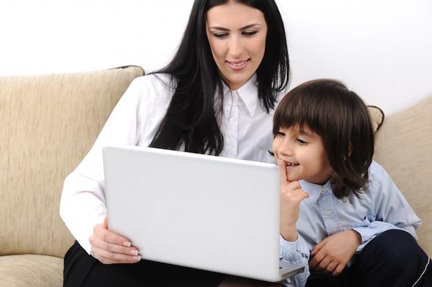 Mère et fils avec ordinateur portable sur le canapé ensemble