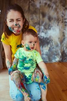 La mère avec fils peignant un grand papier avec leurs mains
