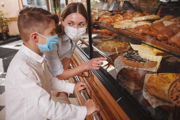 Mère et fils portant un masque médical, faisant du shopping à la boulangerie pendant la pandémie de coronavirus