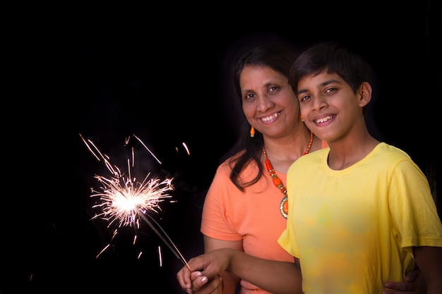 Mère et fils profitant du feu d'artifice étincelant dans le cadre de la célébration du festival de diwali